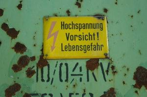 Auf dem Bild sieht man ein Schild, auf dem vor Hochspannung gewarnt wird. Bei Arbeiten an solchen Anlagen müssen unbedingt die 5 Sicherheitsregeln aus dem Elektro-Bereich beachtet werden.
