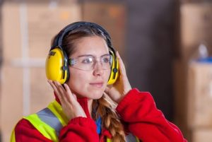 In diesem Bild sehen Sie eine Dame mit ihrer persönlichen Schutzausrüstung. Im § 5 des Arbeitsschutzgesetzes ist vorgeschrieben, dass der Arbeitgeber die Arbeitsbedingungen auf Gefahren zu prüfen hat.