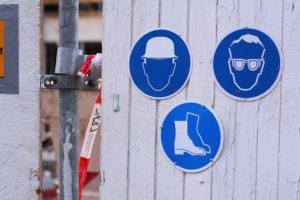 Auf dem Bild sehen Sie Sicherheitshinweise, welche Schutzkleidung auf der Baustelle getragen werden muss. Die Maßnahmen ergaben sich nach der Gefahrenbeurteilung, die im Arbeitsschutzgesetz festgeschrieben ist.