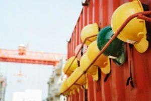 Auf dem Bild sind eine Reihe von Schutzhelmen zu sehen. Sie sind wichtig zur Einhaltung des Arbeitsschutzes, der im Arbeitsschutzgesetz zusammengefasst ist.