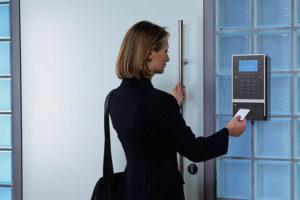 Auf dem Bild ist eine Frau zu sehen, die sich in einem Zeiterfassungssystem einloggen möchte. Arbeitgeber sind nach dem Arbeitszeitgesetz verpflichtet, Überstunden zu dokumentieren.