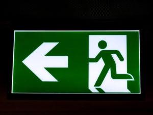 Das Zeichen beschreibt die Richtung zum nächstgelegenen Notausgang. Im Notfall sollten deshalb diese Fluchtwege genutzt werden.