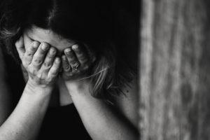 Das Foto zeigt eine Person, die sich schämt. Menschen, die sexuelle Belästigung erlebt haben schämen sich oft für den Vorfall. Sie sollten ihn aber immer melden.